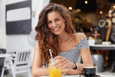 Cheerful relaxed female model enjoys breakfast in cafeteria and cozy atmosphere, drink fresh fruit beverage and coffee, talks with someone. Pleasant looking woman drinks cup of espresso in outdoor bar